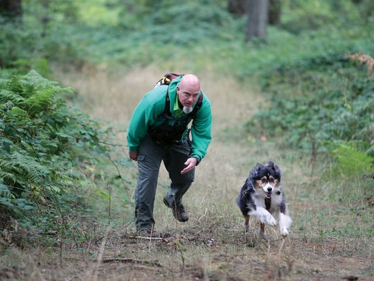 Travis Hull of Kitsap County Search Dogs, has his dog Cody run to the found lost subject Carri Coulter in the woods during a K9 search and rescue training exercise on Saturday near the Bremerton National Airport.