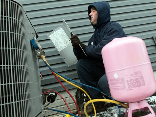 Chad Ordway, of McCleary Heating and Cooling, checks heat pump condensers at a Chambersburg home on Thursday, January 4, 2018. As temperatures drop, some homeowners are experiencing heating problems.