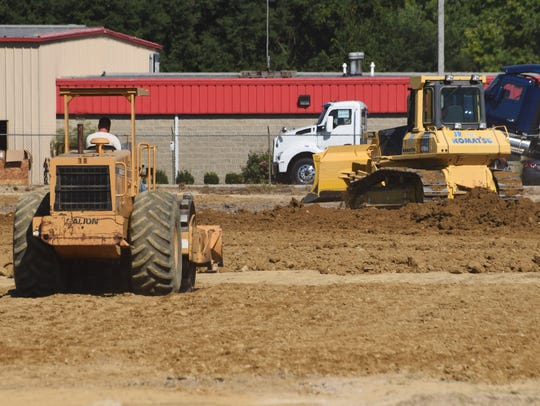 A construction crew works on the site of a new industrial