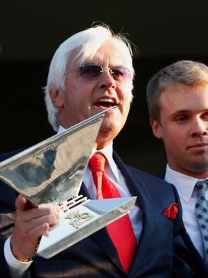 Bob Baffert, trainer for American Pharoah holds the Triple Crown Trophy after American Pharoah won the 147th running of the Belmont Stakes horse race at Belmont Park, Saturday, June 6, 2015, in Elmont, N.Y.