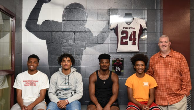 Fulton High senior football players Reg'Onte Jones, Coryean Davis, Dorian Williamson and Joey Smith pose in front of the memorial wall for Zaevion Dobson with head coach Rob Black.