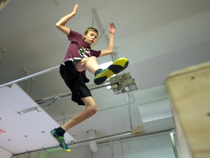 Grant Pemberton, 13, practices Parkour, the sport of free running on various obstacles, generally done in urban spaces, at Apex Movement gym in Loveland Wednesday, April 9, 2014. The gym has been open about 6 months and offers all level of classes.