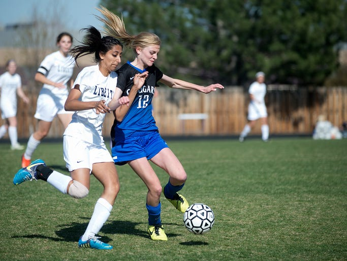 Liberty's Nisha Gill, left, chases down the ball next to Resurrection's Rachel Meyers during a game at Liberty Commons School in Fort Collins Thursday, April 17, 2014.