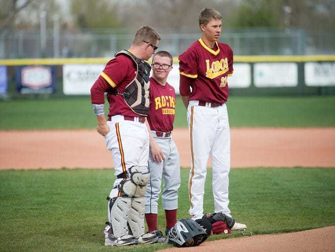 Senior Matt McNeil, center, stands with Rocky Mountain High School baseball teammates Garrett Hammer, left, and Marc Bachman for the National Anthem before throwing out the first pitch at the Lobos' final home game against Greeley West in Fort Collins Tuesday, April 29, 2014. McNeil, who has Down's Syndrome, has been the team's manager for 3 years.