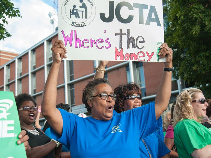 Candace Foster, a retired teacher from Kammerer Middle School protests with other teachers parents and union workers before the JCPS Board of Education meeting at the Van Hoose Education Center on Newburg Road. July 28, 2014