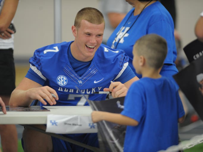 Freshman quarterback Drew Barker laughs with a young fan during the University of Kentucky football fan day at the UK Nutter Training Cente in Lexington, KY. Saturday, August 9, 2014.