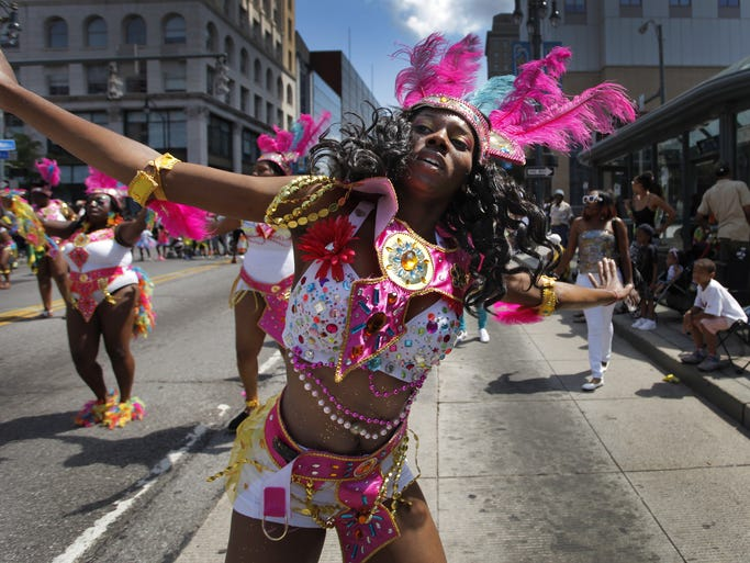Shaniqua Porter, 18, of Rochester dances down Main Street downtown with the People of Paradise dancers during the 30th annual Carifest Parade on Saturday.