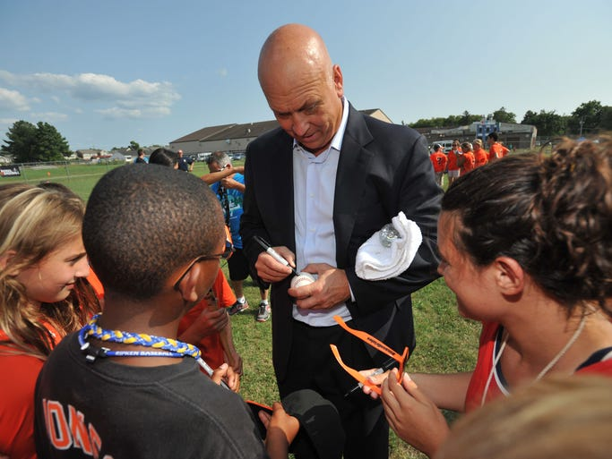 Cal Ripken Jr., left, signs autographs for youth that are in the Badges for Baseball program at the Richard A. Henson Family YMCA.