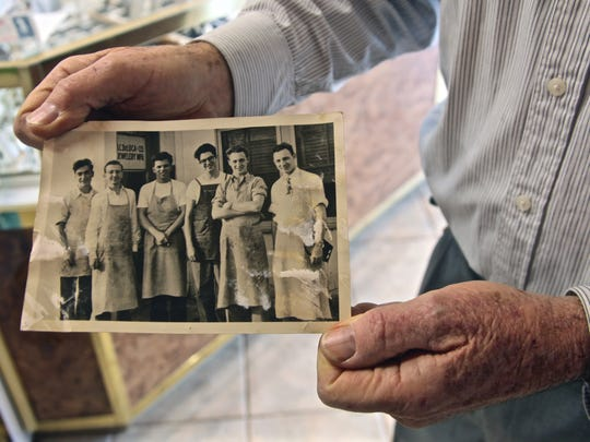 Tony DeLuca holds a photograph that shows himself (second