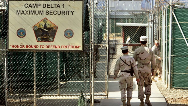 In this June 2006 file photo, reviewed by a U.S. Department of Defense official, U.S. military guards walk within Camp Delta military-run prison, at the Guantanamo Bay U.S. Naval Base, Cuba.