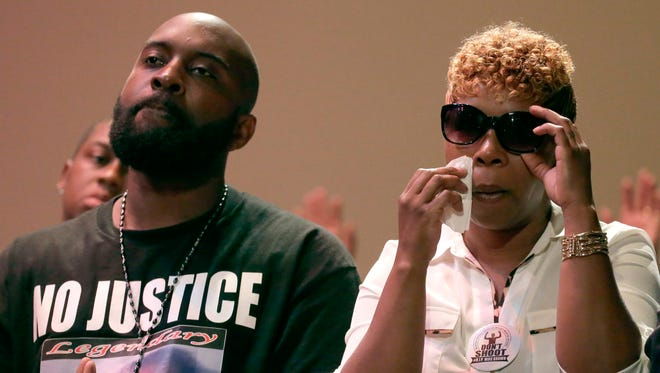 Parents of Michael Brown, Michael Brown Sr. and Lesley McSpadden listen to a speaker during a rally Aug. 17, 2014, for their son who was killed by police.