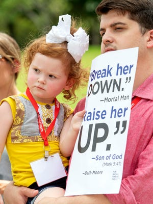 Chase Crawford, a Southern Baptist Convention messenger from Arkansas, and his 2-year-old daughter Chloe Jean Crawford listen to speakers during a rally protesting the Southern Baptist Convention's treatment of women on Tuesday, June 12, 2018 outside the convention's annual meeting at the Kay Bailey Hutchison Convention Center in Dallas.