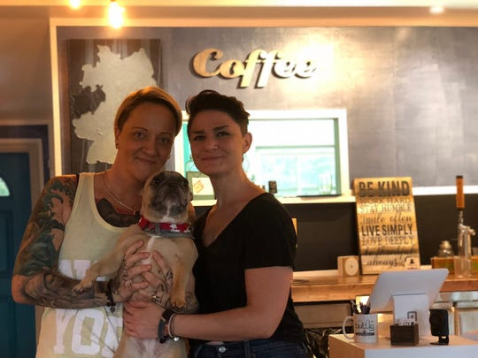 Sabrina Schoellchen and partner Angela Pegan pose with French bulldog Gilly.