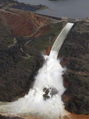 FILE - In this Feb. 13, 2017, file photo, water flows down the damaged spillway at Oroville Dam, in Oroville, Calif. Over six days, operators of the tallest dam in the United States, struggled to figure out their next move after raging floodwaters from California's wettest winter in decades gouged a hole the size of a football field in the dam's main water-release spillway.