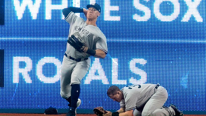 New York Yankees' Aaron Judge throws the ball as Yankees' Billy McKinney drops to the ground after jumping into the wall trying to catch a ball hit by Toronto Blue Jays' Josh Donaldson in the first inning of a baseball game in Toronto on Saturday, March 31, 2018.