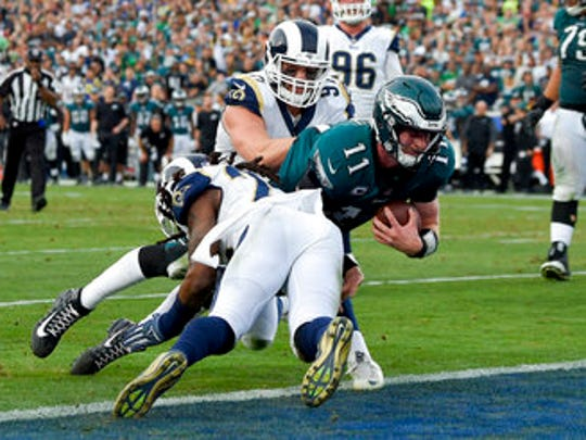 Eagles quarterback Carson Wentz dives into the end zone late in the third quarter Sunday. He apparently hurt his knee on the play, which didn't count because of a penalty. Wentz left the game shortly after that.