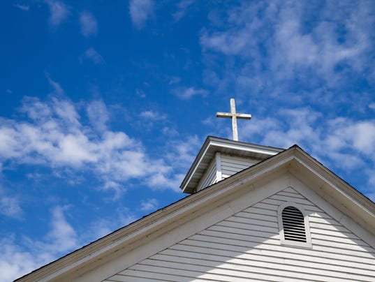 Steeple And Cross Set Against A Blue Sky