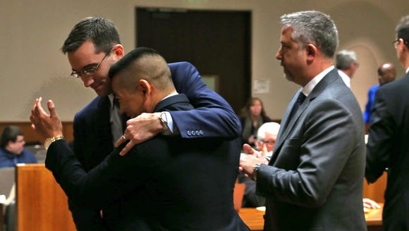 Charles Tan reacts with his defense team after charges