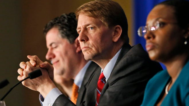 Consumer Financial Protection Bureau Director Richard Cordray, with hands folded.