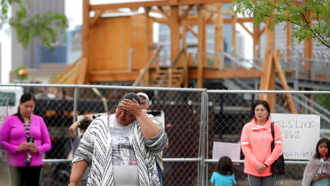 "Crystal Norcross, a Sisseton Wahpeton Dakota from Sisseton S.D., speaks to a crowd gathered near the Walker Sculpture Garden Saturday, May 27, 2017, in Minneapolis. The Walker Art Center in Minneapolis said Saturday it will remove ""Scaffold,"" a two-story sculpture from 2012 by Los Angeles artist Sam Duranta, because of protests from Native Americans who say it brought back painful memories of the mass hanging of 38 Dakota men in 1862."