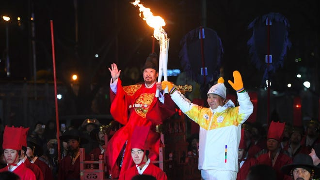 "A ""royal"" torchbearer passes the Olympic flame to the Winter Games  torchbearer in Seoul, South Korea, on Jan. 13, 2018."