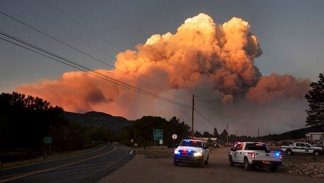 In this photo taken Thursday, May 31, 2018 and provided by Taosnews.com, officials confer as smoke rises from the Ute Park Fire in Ute Park, N.M. Evacuation centers have been set up in northeastern New Mexico as heavy smoke from a wildfire has forced residents from Cimarron and the surrounding areas to leave their homes. Authorities were directing people to the communities of Springer and Raton as conditions were expected to worsen Friday, June 1, 2018.