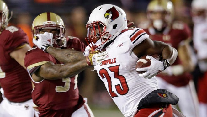 Louisville running back Brandon Radcliff (23) picks up yardage as he straight-arms Boston College linebacker Sean Duggan (34) during the first quarter of an NCAA college football game  Saturday, Nov. 8, 2014 in Boston. (AP Photo/Stephan Savoia)