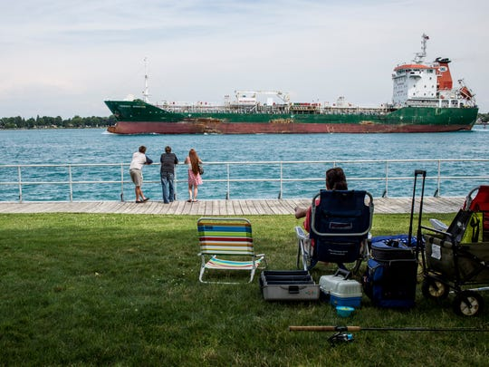 People relax and watch as the freighter Tradewind Adventure passes Thursday, July 28, 2016 on the St. Clair River in St. Clair. The St. Clair Riverfest continues through the weekend, with the St. Clair River Classic Offshore Boat Race beginning at noon Sunday.