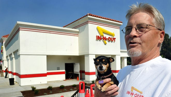 Sam Garrett and Lola of Grants Pass, Ore.,  are ready for Medford's In-N-Out restaurant to open, Wednesday, Aug. 27, 2015 in Medford, Ore. In-N-Out Burger fans are counting the days until their favorite fast-food restaurant opens in Medford, with many unofficial reports indicating Sept. 9 might be the magic day. (Bob Pennell/The Medford Mail Tribune via AP) MANDATORY CREDIT