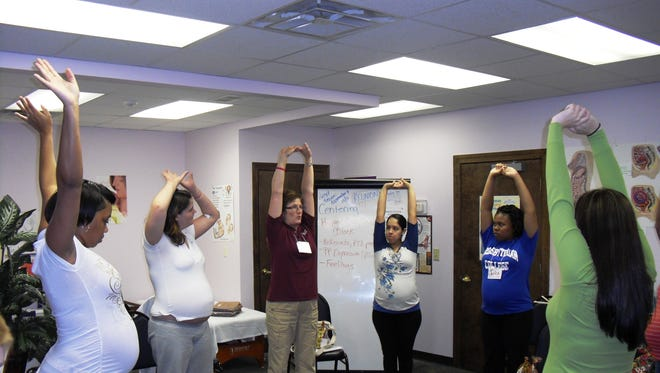 A group of women stretch during a CentergPregnancy meeting.
