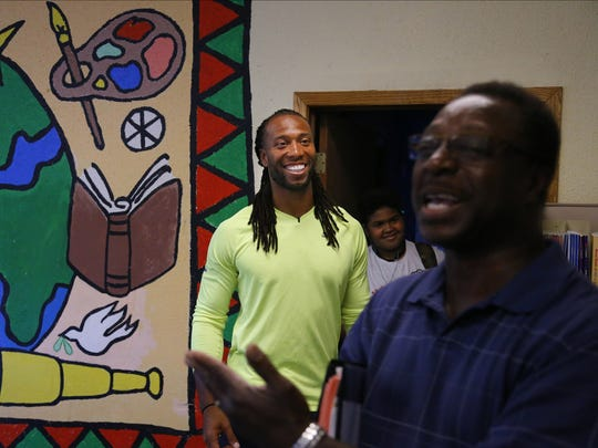 Youth Program Manager Bobby Lay introduces Arizona Cardinals' Larry Fitzgerald as he visits the Sabathani Community Center on July 23.