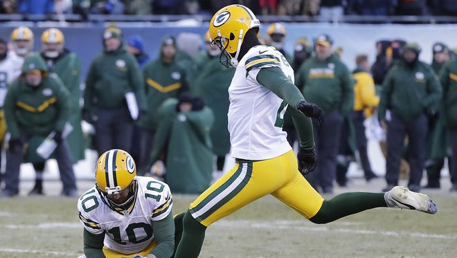 Green Bay Packers kicker Mason Crosby (2) kicks the winning field goal as punter Jacob Schum (10) holds against the Chicago Bears at Soldier Field Sunday, December 18, 2016.