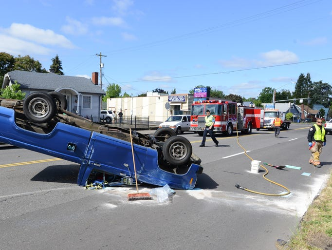 Officials respond to a rollover crash at Market and McCoy streets in Salem on Wednesday, May 21, 2014.