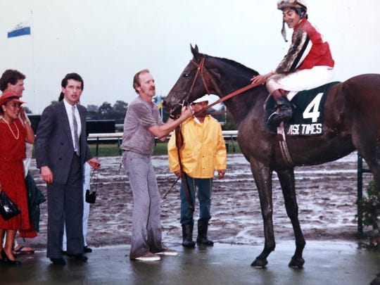 Wise Times, with Chris DeCarlo riding, in the winner's circle after the $300,000 Grade 1 Haskell Invitational on July 26, 1986.Trainer Phil Gleaves is in the suit on the left.