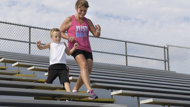 Nicole O'Dell works out with her son, Logan, in Paxton, Ill. The 43-year-old mother of six children (ages 24, 18, 15 and 7-year-old triplets) has lost 106 pounds in a year. She's a full-time marketing manager, a graduate student, and maintains a website — www.fitandbusylife.com.