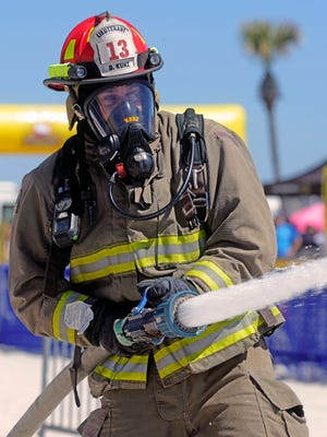 Escambia County firefighter Lt. Dan Kunz of team Protectors of the Sandbox, does the charged hose pull during the team competition Saturday during the Beach Firefighter Challenge at Pensacola Beach. The course is comprised of five obstacles based on skills firefighters use every day. They are forced entry, charged hose pull, Kaiser Sled, mannequin drag and hose hoist. One hundred firefighters from five states competed in the competition.