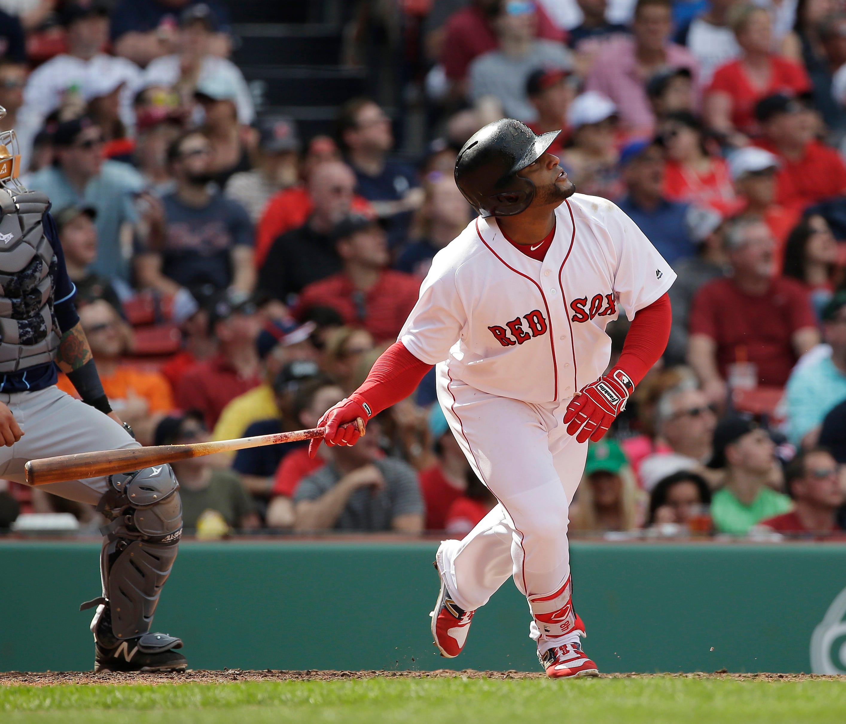 Boston Red Sox's Pablo Sandoval, right, watches the flight of his two-run home run as Tampa Bay Rays catcher Jesus Sucre, left, looks on in the fourth inning of a baseball game, Sunday, April 16, 2017, in Boston. (AP Photo/Steven Senne)