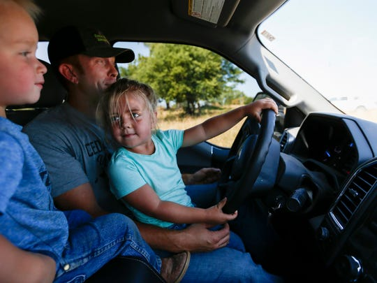 Three-year-old Willa Grace pretends to drive as she sits on her dad Billy Bruce's lap while her brother Jacob, 2, looks on as they drive across a field on their farm in rural Cedar County on Friday, July 13, 2018.