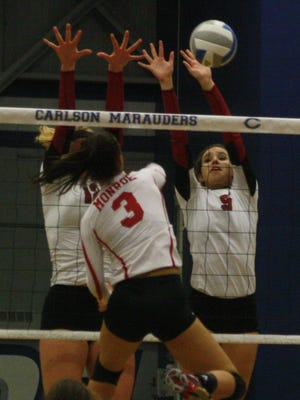 Churchill's Sam Zonca (9) and Anne Yost (obscured) rise to block a hit by Monroe's MacKenzie Boatman.