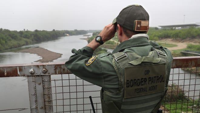 A U.S. Border Patrol agent scans the U.S.-Mexico border while on a bridge over the Rio Grande on March 13, 2017, in Roma, Texas.