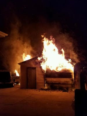 The garage fire destroyed two vehicles, one in the garage and one parked adjacent.