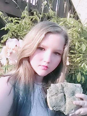 Ryleigh Taylor, 11, poses with the fossil she discovered.