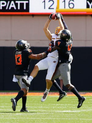 Central Michigan Chippewas wide receiver Jesse Kroll (88) goes up for a catch as Oklahoma State Cowboys safety Jordan Sterns (13) and cornerback Lenzy Pipkins (4) defend during the first quarter at Boone Pickens Stadium.