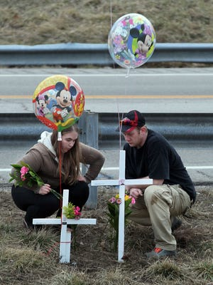 Elizabeth Napier and Jason May, parents of 13 month-old twins Sean and Samantha, who with their grandfather Charles Napier  were struck and killed by a car on Weaver Road, pause after erecting crosses with balloons near the spot where their children were killed.