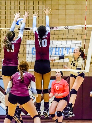 Breann DeLoye, left, of Okemos blocks a hit by Allie Peterson, right, of Holt early in the third game of their match in 2015.