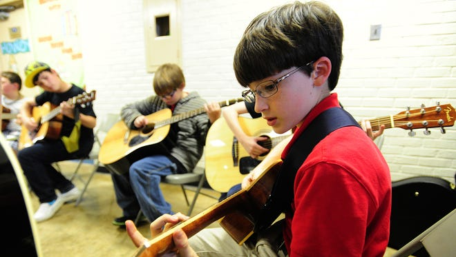 Andrew Caffery, 11, plays along with fellow students as they learn blues and rock guitar techniques from Chad Viator during the Guitar Family Jam at L.J. Alleman Arts Academy in Lafayette.