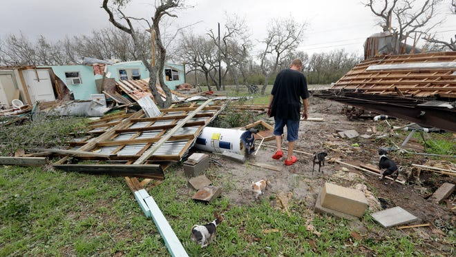 Sam Speights walks with his dogs as he checks on the damage to his home in the wake of Hurricane Harvey, Sunday, Aug. 27, 2017, in Rockport, Texas. Speights tried to stay in his home during the storm but had to move to other shelter after his lost his roof and back wall. (AP Photo/Eric Gay)