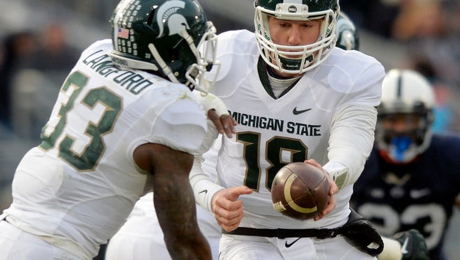 Michigan State quarterback Connor Cook hands the ball to Jeremy Langford during the first half of an NCAA college football game against Penn State in State College, Pa., Saturday, Nov. 29, 2014.