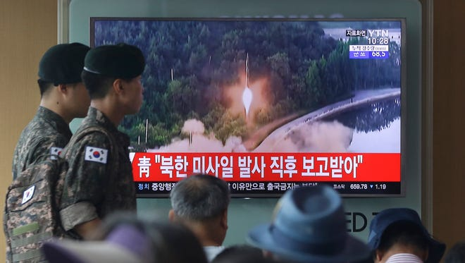 South Korean Army soldiers walk by a TV news program showing a file image of a missile being test-launched by North Korea at the Seoul Railway Station in Seoul, South Korea.