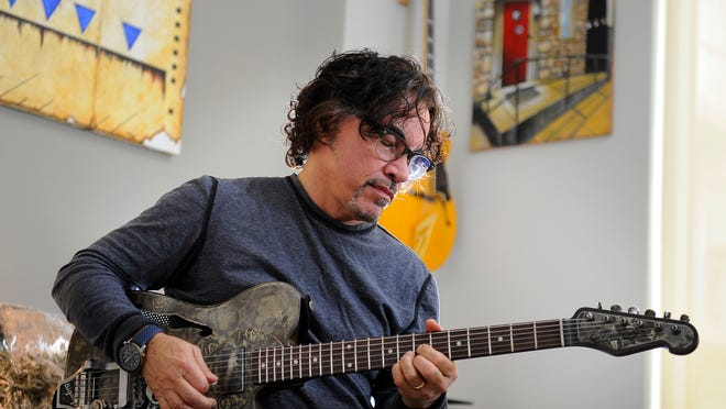 John Oates plays one of his guitars at his Gulch condominium in Nashville.
